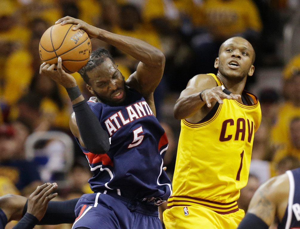 . Atlanta Hawks\' DeMarre Carroll (5) grabs a rebound against Cleveland Cavaliers\' James Jones (1) during the first half in Game 3 of the Eastern Conference finals of the NBA basketball playoffs Sunday, May 24, 2015, in Cleveland. (AP Photo/Tony Dejak)