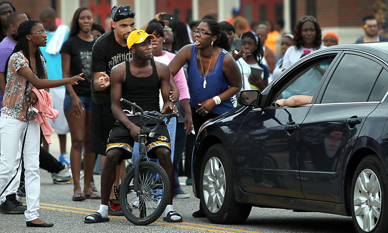 . Protestors blocking Florissant Road block a motorist who tries to get through their sit-in in front of the Ferguson, Mo., police department on Sunday, Aug. 10, 2014, one day after a Ferguson officer shot and killed Michael Brown. (AP Photo/St. Louis Post-Dispatch, Robert Cohen)