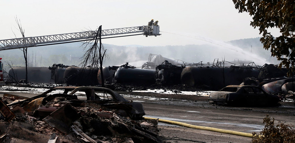 . Firefighters work at the scene of a train derailment in Lac Megantic, Quebec, July 7, 2013.  A driverless freight train carrying tankers of petroleum products derailed at high speed and exploded into a giant fireball in the middle of the small Canadian town of Lac-Megantic early on Saturday, destroying dozens of buildings and leaving an unknown number of people feared missing.  REUTERS/Christinne Muschi