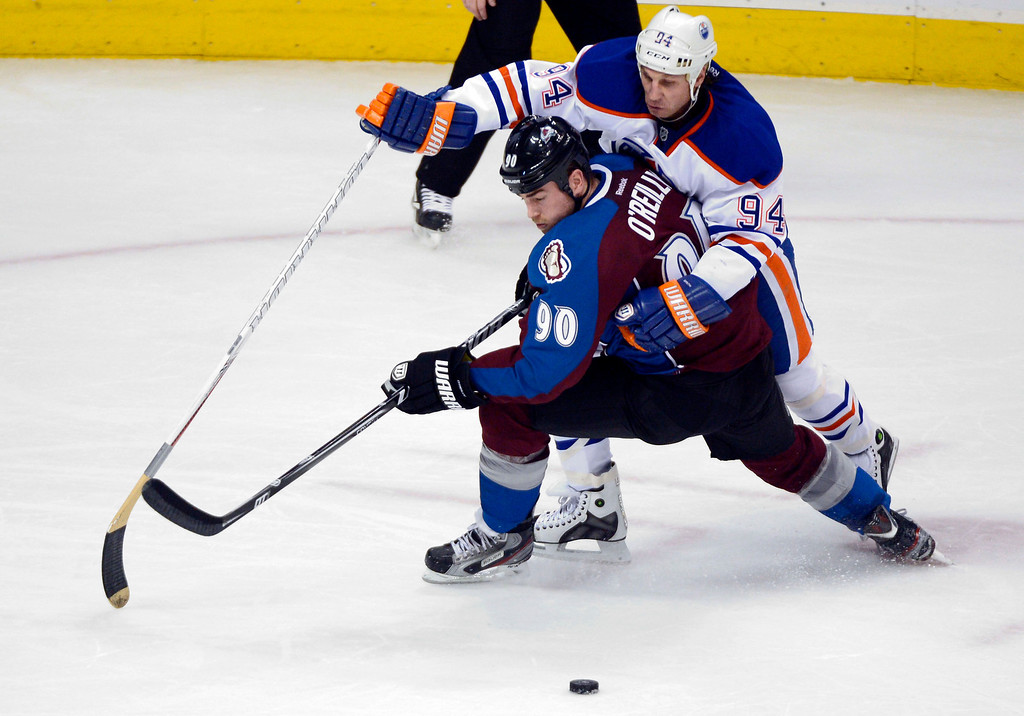 . Ryan Smyth (94) of the Edmonton Oilers tries to go over Ryan O\'Reilly (90) of the Colorado Avalanche to get to the puck during the second period March 12, 2013 at Pepsi Center. (Photo By John Leyba/The Denver Post)
