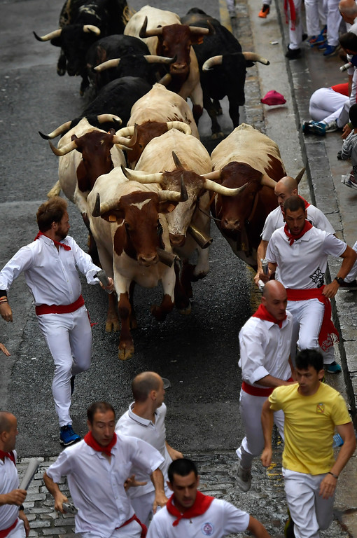 . Revellers run in front of Puerto de San Lorenzo\'s fighting bulls during the running of the bulls at the San Fermin Festival, in Pamplona, northern Spain, Saturday, July 7, 2018. Revellers from around the world flock to Pamplona every year to take part in the eight days of the running of the bulls. (AP Photo/Alvaro Barrientos)