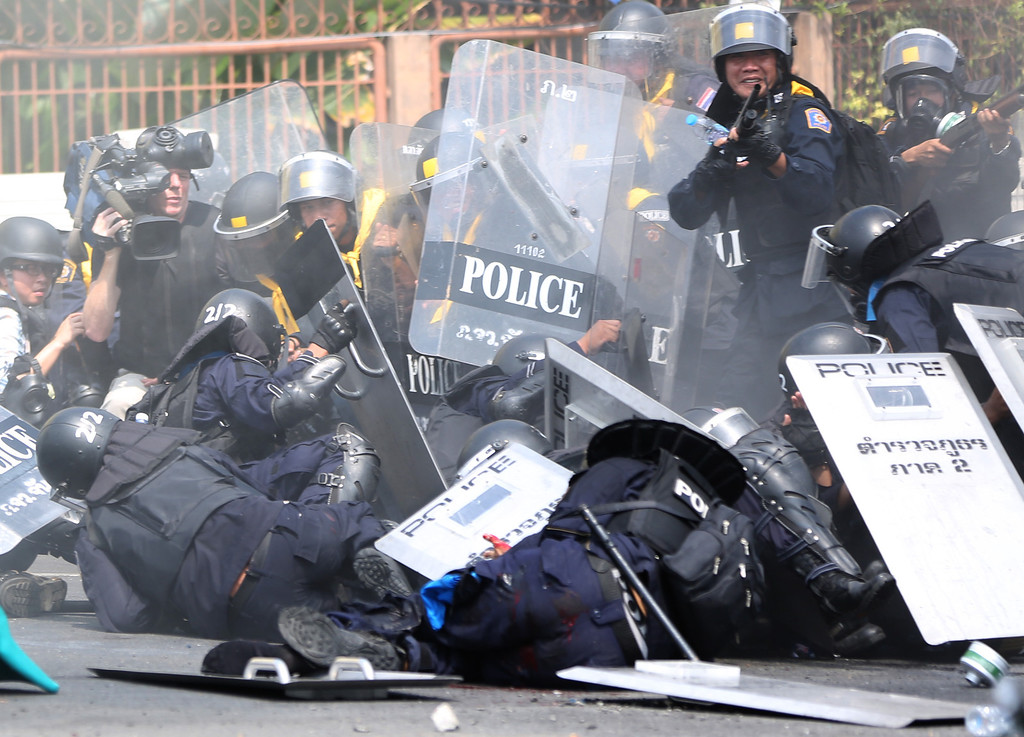 . Riot police officers fall on the ground after a bomb blast near them during a clash with anti-government protesters Tuesday, Feb. 18, 2014 in Bangkok, Thailand. (AP Photo/Apichart Weerawong)