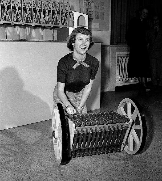 . Joan Kramiller of Detroit gets a bang out of the triple-tier machine gun which was designed by Leonardo Da Vinci, Renaissance artist and scientist. This model was constructed by Roberto Guatello and is one of 68 mechanical conceptions based on Da Vinci sketches which were on view at The Edison Museum in Dearborn, Mich., Jan. 19, 1950. The machine gun has twelve guns in each tier. One tier was to be fired while a second was being loaded and the third was cooling. (AP Photo/Preston Stroup)