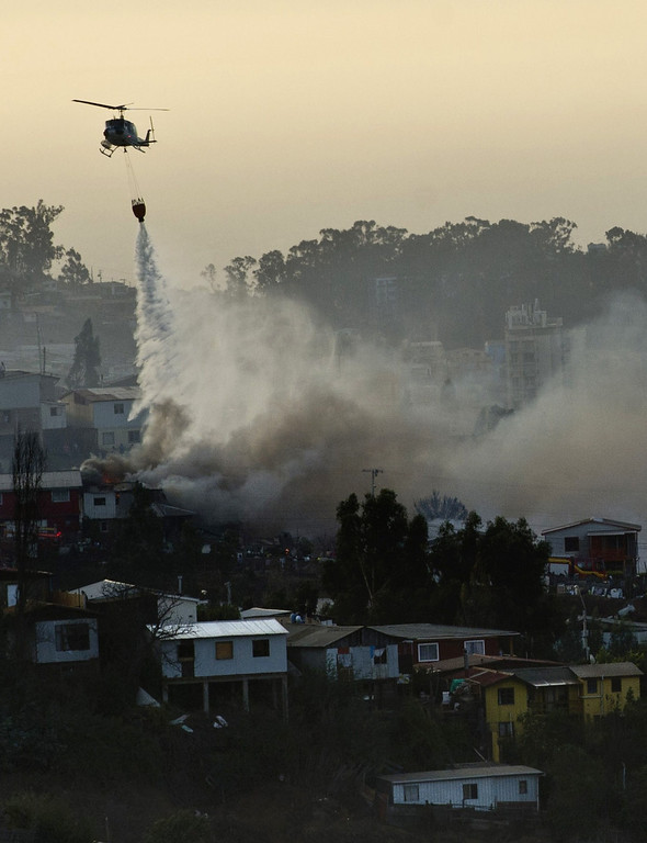 . A helicopter works after some focuses reactivated, in Valparaiso, Chile, on April 13, 2014. More than 10,000 people were evacuated as an army of firefighters battled a killer blaze that --on the eve-- tore through parts of Chile\'s historic port of Valparaiso and left at least 11 people dead. The fire, which started in woodland Saturday, gutted 500 homes as flames advanced on the city of 270,000, famed for its UNESCO-listed center with cobblestone streets and brightly painted wooden homes. AFP PHOTO/MARTIN BERNETTI