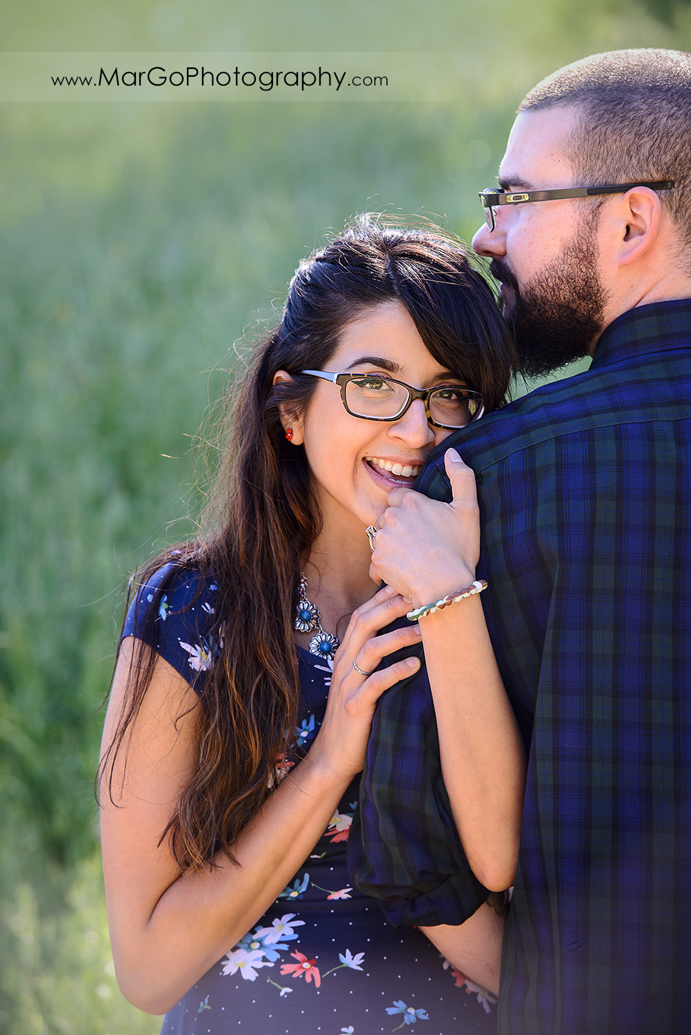 portrait of woman in blue dress looking into camera and holding hands on arm of man in blue shirt during engagement session at Sunol Regional Wilderness