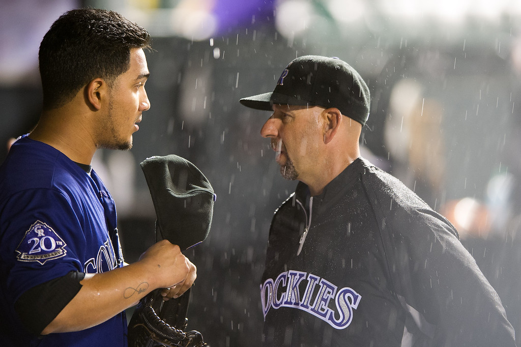. Jhoulys Chacin #45 and manager Walt Weiss #22 of the Colorado Rockies have a talk between innings as rain falls during a game against the San Diego Padres at Coors Field on August 12, 2013 in Denver, Colorado. A rain delay was called in the eighth inning with the Rockies leading 8-1.  (Photo by Dustin Bradford/Getty Images)