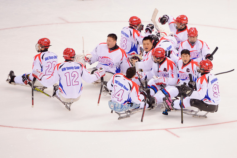 . Players of Korea celebrate after winning their Ice Sledge Hockey Preliminary Round Group A match against Russia at Shayba Arena on March 8, 2014 in Sochi, Russia.  (Photo by Dennis Grombkowski/Getty Images)