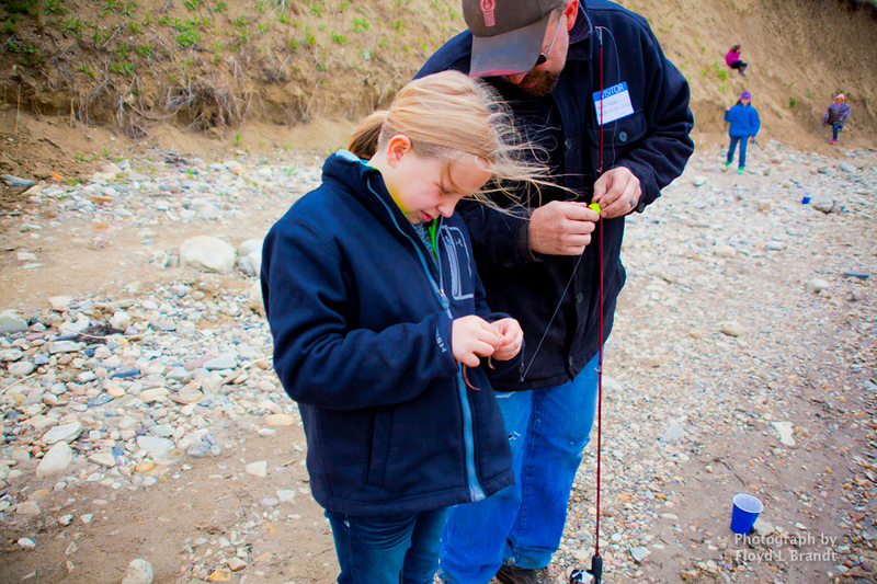 Havre Daily News/Floyd Brandt  Lynsie Molitor is a true fieherman, putting the worm on the hook as her dad stands by to giver her help at Beaver Creek Reservoir Wednesday. Montana Fish and Wildlife gave a short lecture on how to catch fish and provided fishing-poles for Lincoln-McKinley 3rd grade classes..