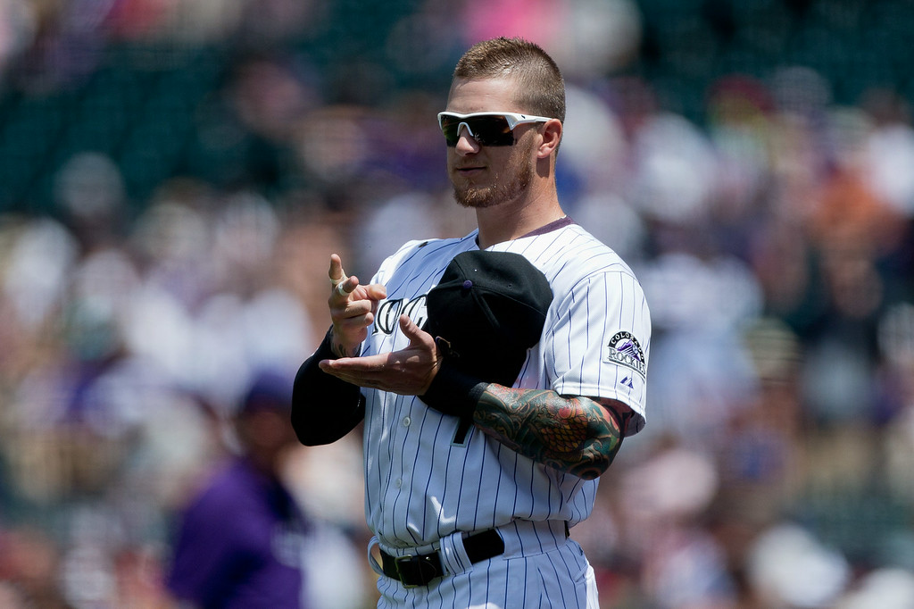 . DENVER, CO - JULY 23:  Brandon Barnes #1 of the Colorado Rockies plays paper, rock, scissors with a member of the Washington Nationals during a friendly standoff before the game started at Coors Field on July 23, 2014 in Denver, Colorado. (Photo by Justin Edmonds/Getty Images)