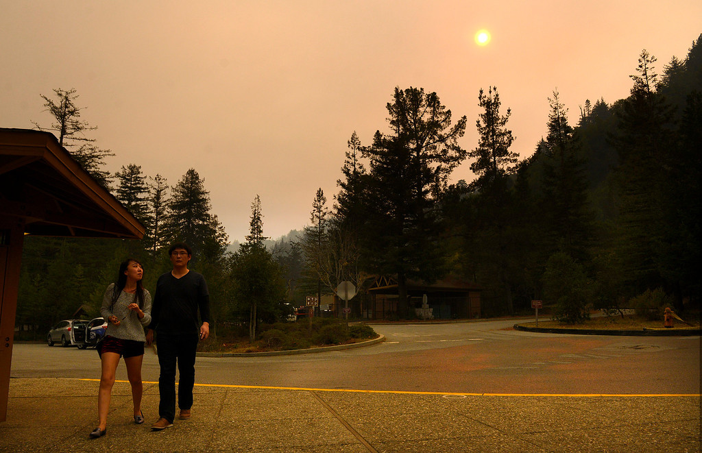 . Han Meng, left, looks up at the smoke and ash filled sky while walking to the Big Sur Station with Zhi Yang, both of China, as firefighters battle a wildland fire in the Pfeiffer Ridge area in Big Sur on Monday December 16, 2013. (Photo David Royal/ Monterey County Herald)