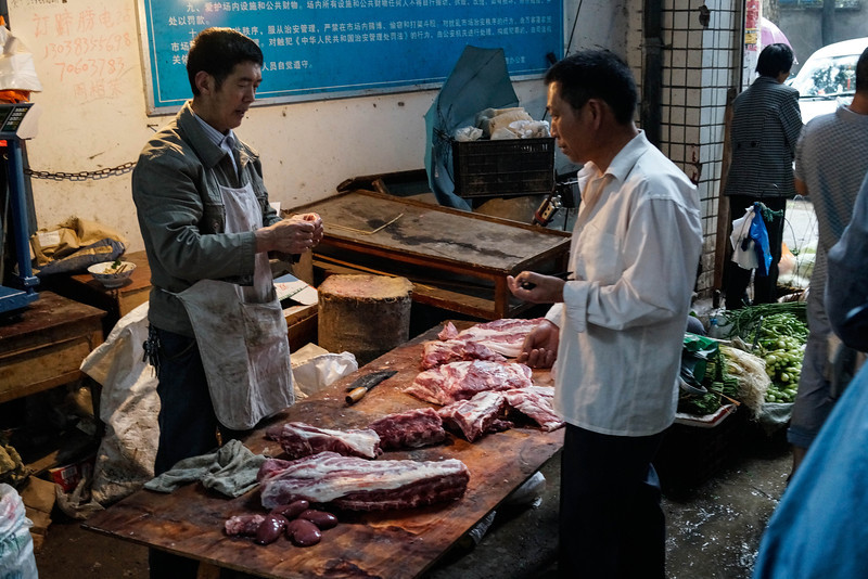 Fengdu - Butchers in meat section of local super market.
