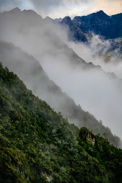 Whispy clouds cover green mountainsides in Peru