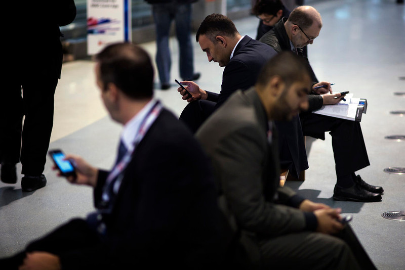 . Attendees use their devices inside a pavilion at the Mobile World Congress, the world\'s largest mobile phone trade show, in Barcelona, Spain, Tuesday, Feb. 26, 2013. (AP Photo/Emilio Morenatti)