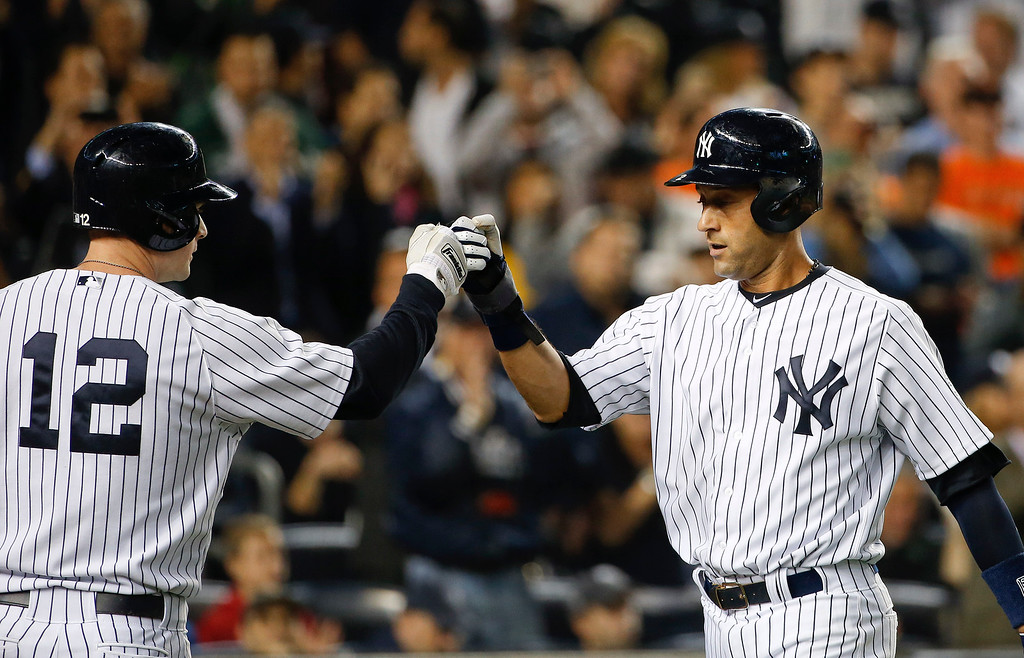 . New York Yankees\' Derek Jeter, right, is greeted at home plate by Chase Headley after scoring against the Baltimore Orioles in the first inning of a baseball game, Thursday, Sept. 25, 2014, in New York. (AP Photo/Kathy Willens)