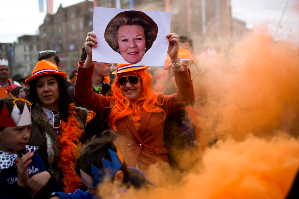 . People, one of them holding a picture of Princess Beatrix, react as King Willem-Alexander, Queen Maxima and Princess Beatrix sign the act of abdication outside the Royal Palace in Amsterdam, The Netherlands, Tuesday April 30, 2013. Around a million people are expected to descend on the Dutch capital for a huge street party to celebrate the first new Dutch monarch in 33 years.  (AP Photo/Emilio Morenatti)
