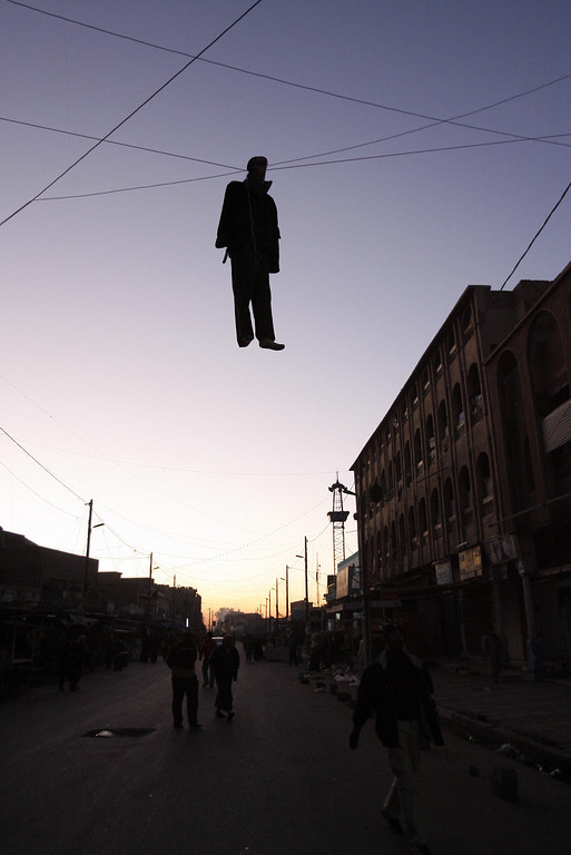 . An effigy of Saddam Hussein hangs in a central Baghdad street 30 December 2006, as Iraqis reeled from the news that ousted Iraqi despot Saddam Hussein was executed by hanging. More than 50 Iraqis were killed and dozens more wounded in a series of bloody car bombings that caused chaos after the government\'s pre-dawn execution of Saddam Hussein. (AHMAD AL-RUBAYE/AFP/Getty Images)