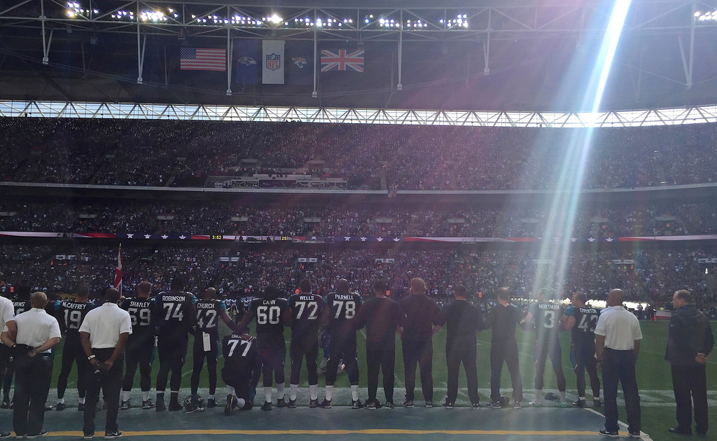 . Jacksonville Jaguars offensive lineman Patrick Omameh (77), center, kneels down during the playing of the US national anthem before an NFL football game against Baltimore Ravens at Wembley Stadium in London, Sunday Sept. 24, 2017. (AP Photo/Tony Hicks)