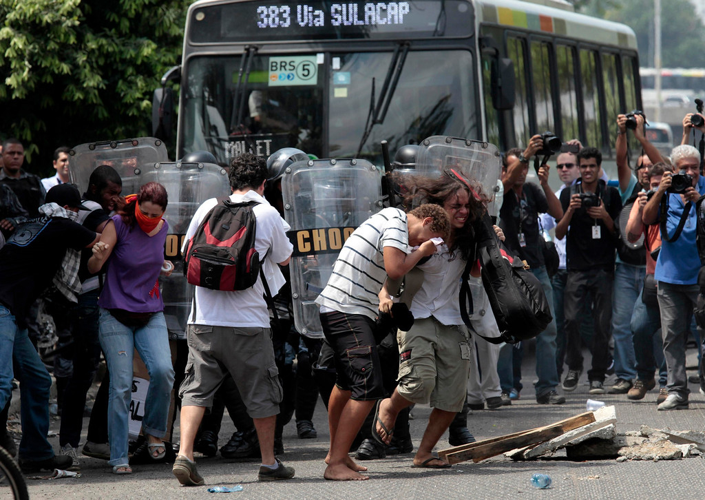 . Supporters of the native Indian community clash with riot police near the Brazilian Indian Museum in Rio de Janeiro March 22, 2013. Brazilian military police took position early morning outside the abandoned Indian museum, where a native Indian community of around 30 individuals have been living since 2006. The Indians were summoned to leave the museum in 72 hours by court officials since last week, local media reported. The group is fighting against the destruction of the museum, which is next to the Maracana Stadium.  REUTERS/Sergio Moraes