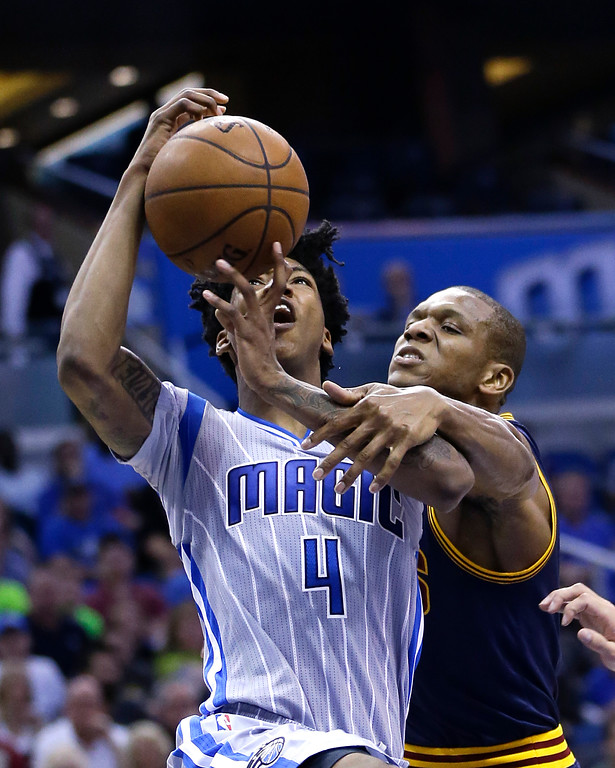 . Orlando Magic\'s Elfrid Payton (4) loses the ball as he is fouled by Cleveland Cavaliers\' James Jones, right, while going up for a shot during the second half of an NBA basketball game, Sunday, March 15, 2015, in Orlando, Fla. Cleveland won 123-108. (AP Photo/John Raoux)