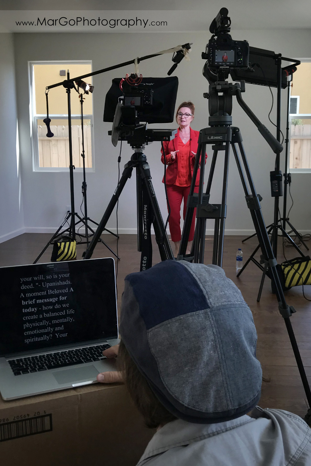 behind the scenes of two cameras setup indoor filming woman speaker in red suit and videographer running teleprompter