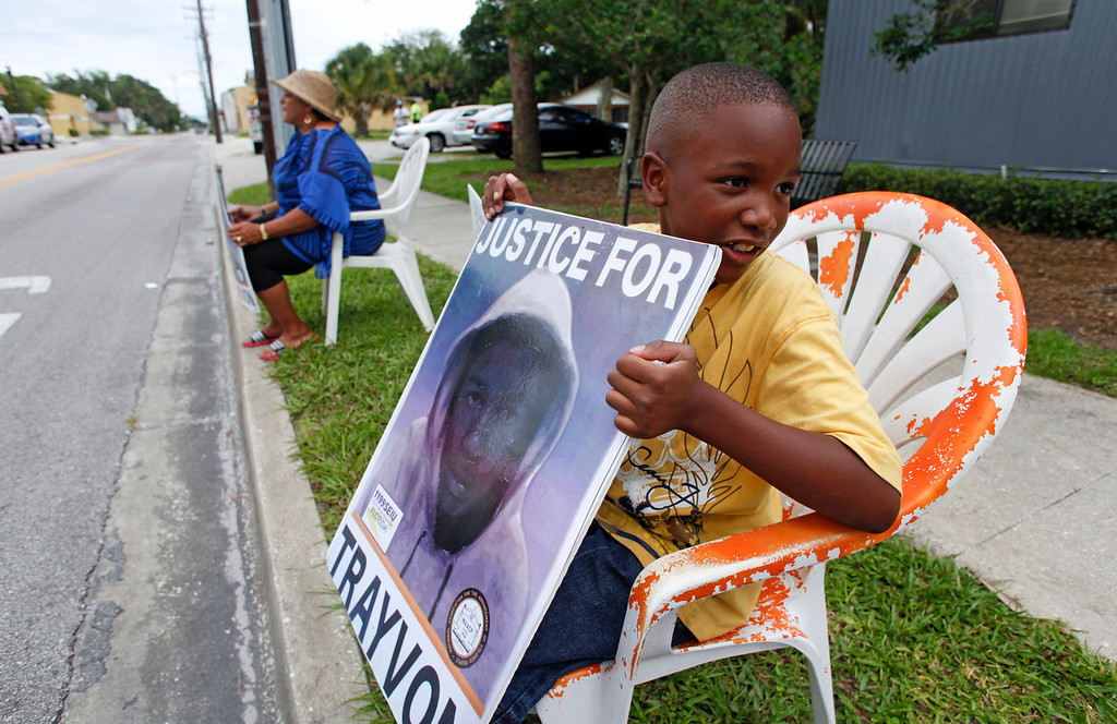 . Antonio McVay, 8, holds a sign in front of his home in the Goldsboro Historical neighborhood, Saturday, July 13, 2013, in Sanford, Fla., while residents wait for word on the verdict in the George Zimmerman trial. Zimmerman has been charged with the 2012 shooting death of Trayvon Martin. (AP Photo/Mike Brown)