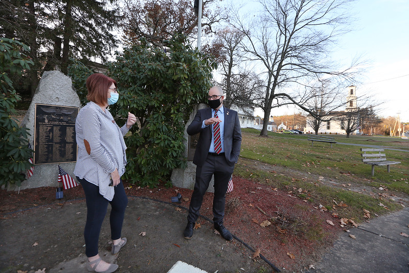 Tyngsboro assistant town administator Justin Sultzbach, and resident Cheryl Manahan, at the current location of the town's war memorials, on town land on Rt 31 that looks like part of front yards. The memorials will be relocated to the park at the town center, and the Vietnam memorial, left, will be restored. (SUN/Julia Malakie)