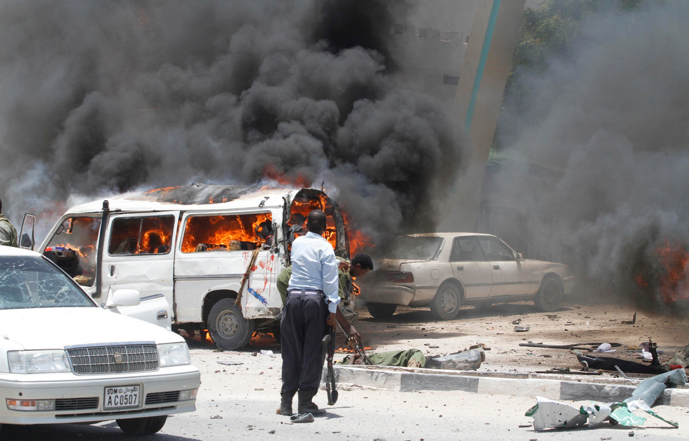 . Policemen attempt to evacuate the remains of their colleagues killed at the scene of an explosion near the presidential palace in Mogadishu March 18, 2013. A car bomb exploded near the presidential palace in the Somali capital Mogadishu on Monday, killing at least 10 people in a blast that appeared to target senior government officials, police said. REUTERS/Feisal Omar