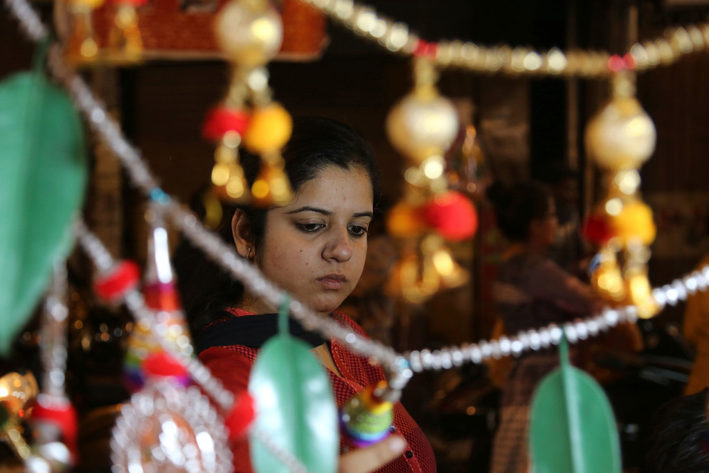 . An Indian woman shops for decorative items on the eve of Diwali, the Hindu festival of lights, in Jammu, India, Wednesday, Oct. 18, 2017. Hindus light up their homes and pray to Lakshmi, the goddess of wealth, during the festival which will be celebrated on Thursday. (AP Photo/Channi Anand)