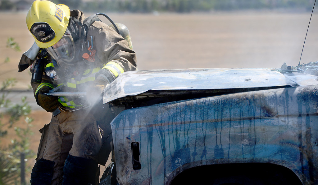 . Ontario firefighter Tommy Pacheco attempts to open the engine hood on a vehicle fire on the Vineyard offramp Thursday May 2, 2013. Marco Perez of Riverside said he smelled gas coming from his truck and pulled over to the shoulder of the Vineyard Avenue offramp of the westbound 10. No one was injured and the cause of the fire is under investigation. (Rick Sforza/Inland Valley Daily Bulletin)