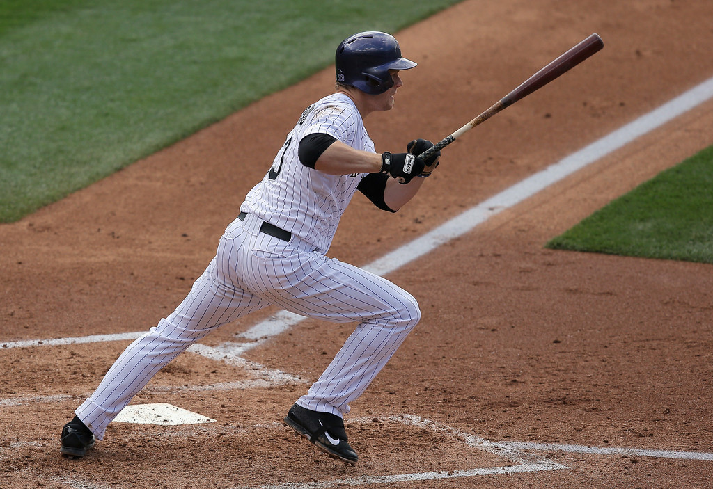 . Justin Morneau #33 of the Colorado Rockies hits a sacrifice grounder to score Carlos Gonzalez #5 of the Colorado Rockies and tie the score 3-3 with the Philadelphia Phillies in the third inning at Coors Field on April 20, 2014 in Denver, Colorado.  (Photo by Doug Pensinger/Getty Images)