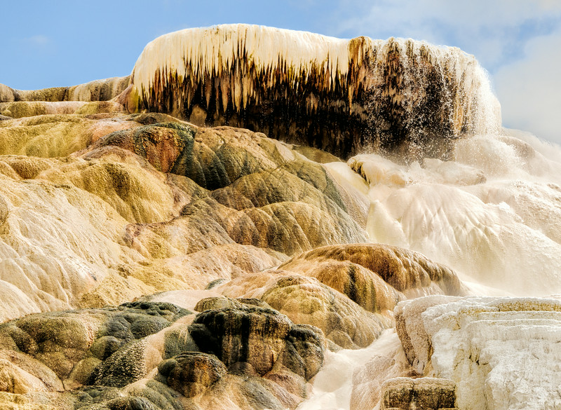 """13 Aug 14.  We'll pick up our walk along the boardwalk in the Lower Terrace of Mammoth Hot Springs and go all the way to the end, roughly another 100 feet or so. Now we are looking directly at Palette Spring and, for lack of a better description, we are watching it being created. Next time you get to look at it it will look different, not only because it is constantly being formed, but also because the lighting will be different. At the time on the stormy day I took this shot the sky was a total bland gray, so I've cheated a bit and substituted another sky from the same shoot that had a bit more color and material in it. The colors you are seeing are what was there when I took the shot, moments later, with the very bright stormy light hiding behind a black cloud, they looked quite different. I thought you might prefer the brighter colors over the duller ones. You can see the water containing the minerals that form the """"rock"""" spilling over the top at the upper right hand corner. The wind was blowing sufficiently that they were not always falling directly over the top but rather being pushed over the side. And depending on which side they were being blown, one had to keep a close eye on the front element of the lens, which on the particular lens I was using had an expendable filter covering it. This is a marvelous place to visit, one where I can stand and watch for prolonged periods of time. Nikon D300s; 18 - 200; Aperture Priority; ISO 200; 1/500 sec @ f / 9."""