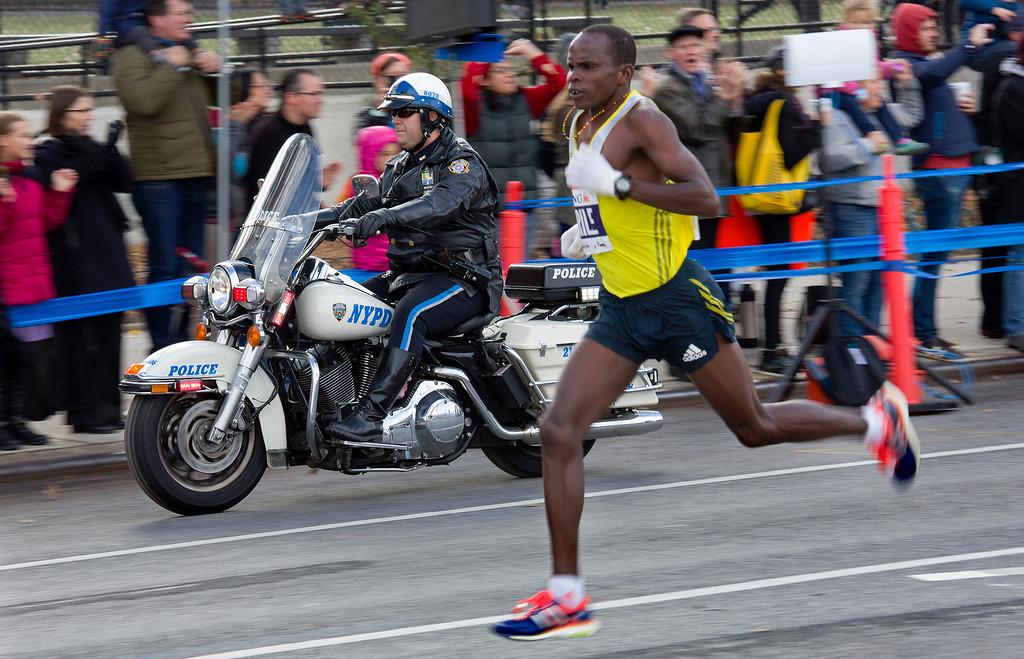 . An New York police office rides alongside Julius Arile of Kenya as he runs in the Brooklyn borough of New York during the New York City Marathon, Sunday, Nov. 3, 2013. (AP Photo/Craig Ruttle)