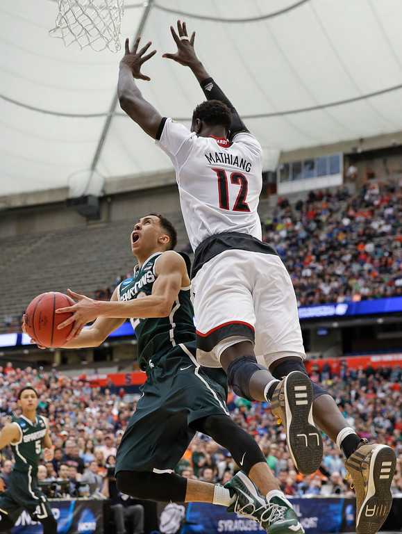 . Michigan State\'s Travis Trice (20) looks to shoot against Louisville\'s Mangok Mathiang (12) during overtime in the NCAA men\'s college basketball tournament regional final, Sunday, March 29, 2015, in Syracuse, N.Y. Michigan State won 76-70. (AP Photo/Seth Wenig)