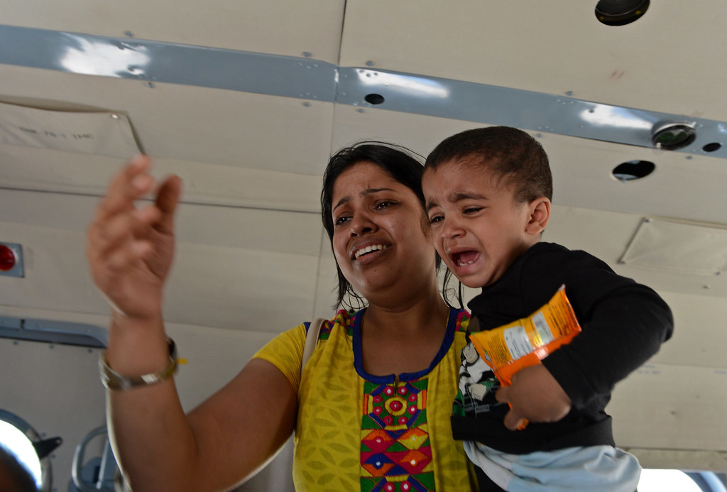 . An Indian tourist reacts as she carries a child inside an Indian Air Force helicopter after being evacuated from a flood-affected area during rescue and relief operations in Srinagar on September 10, 2014.  AFP PHOTO/Tauseef MUSTAFA/AFP/Getty Images