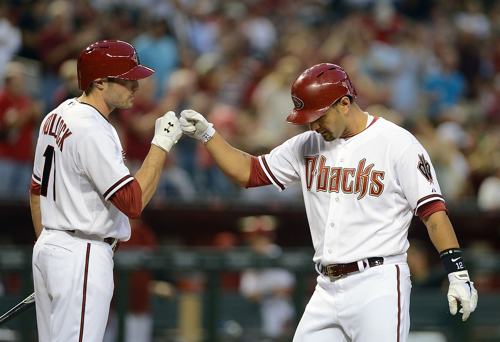 . PHOENIX, AZ - APRIL 26:  Eric Chavez #12 of the Arizona Diamondbacks is congratulated at home plate by teammate A.J. Pollock #11 after hitting a solo home run against the Colorado Rockies in the second inning at Chase Field on April 26, 2013 in Phoenix, Arizona.  (Photo by Jennifer Stewart/Getty Images)