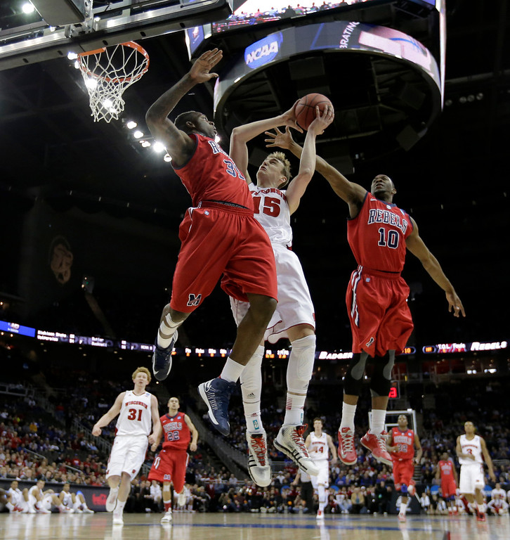 . Wisconsin forward Sam Dekker (15) puts up a shot between Mississippi forward Murphy Holloway (31) and  guard Ladarius White (10) during the first half of a second-round game of the NCAA college basketball tournament Friday, March 22, 2013, in Kansas City, Mo. (AP Photo/Charlie Riedel)