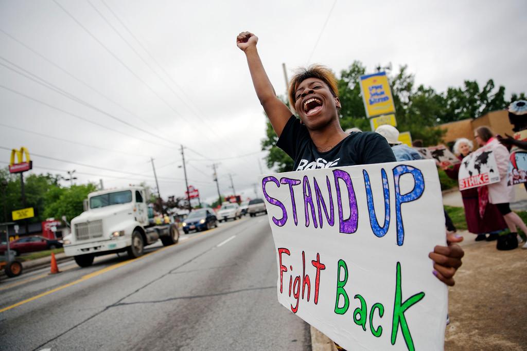 . Carmen Burley-Rawls, 20, shouts to passing motorists during a protest outside a Long John Silver\'s and McDonald\'s restaurant, Thursday, May 15, 2014, in Atlanta. (AP Photo/David Goldman)