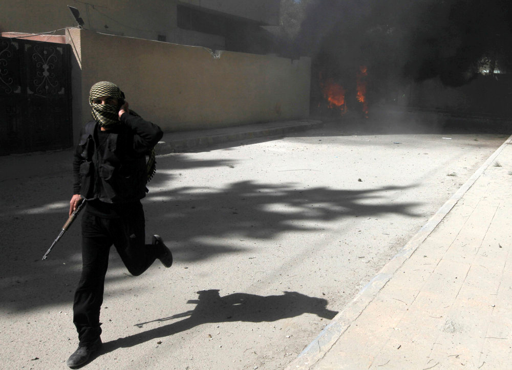 . A fighter from Islamist Syrian rebel group Jabhat al-Nusra runs with his weapon as their base is shelled in Raqqa province, eastern Syria, March 14, 2013. REUTERS/Hamid Khatib