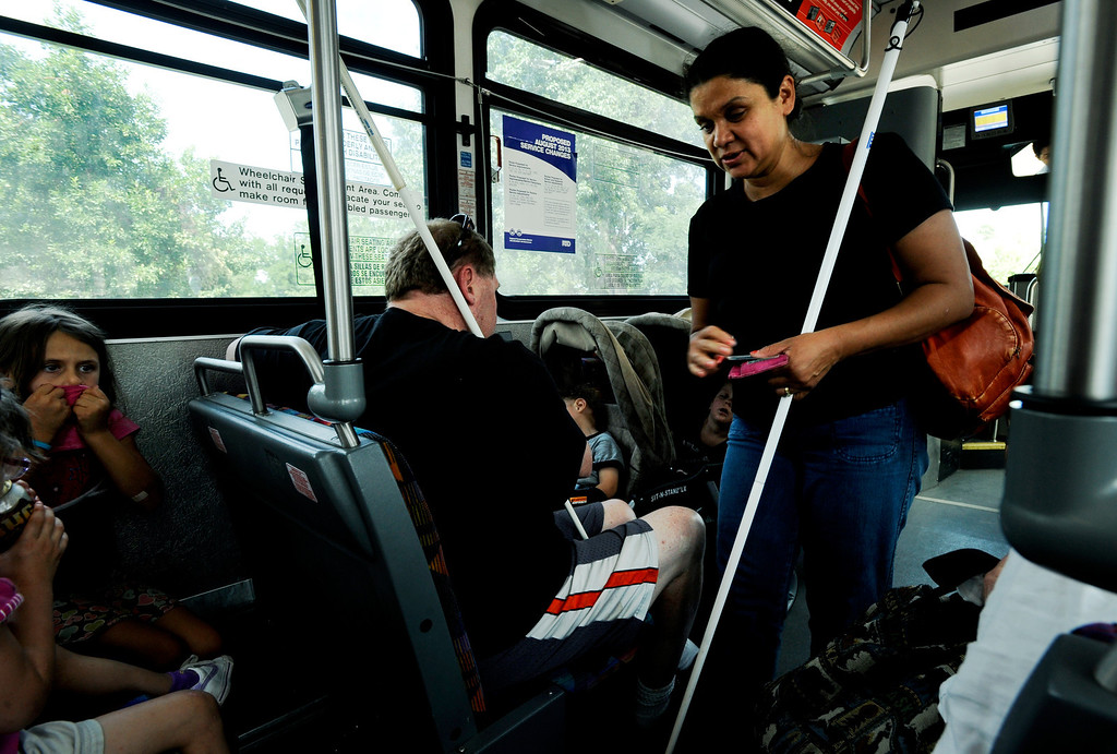. Ena finds a seat on the city bus next to her family. The city\'s metro system and walking are the family\'s two main methods of transportation.  Photo by Jamie Cotten, Special to The Denver Post