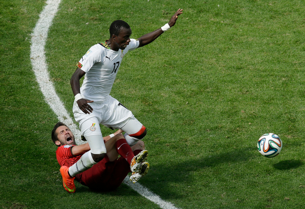 . Ghana\'s Mohammed Rabiu goes for the ball as Portugal\'s Joao Moutinho goes down during the group G World Cup soccer match between Portugal and Ghana at the Estadio Nacional in Brasilia, Brazil, Thursday, June 26, 2014. (AP Photo/Themba Hadebe)