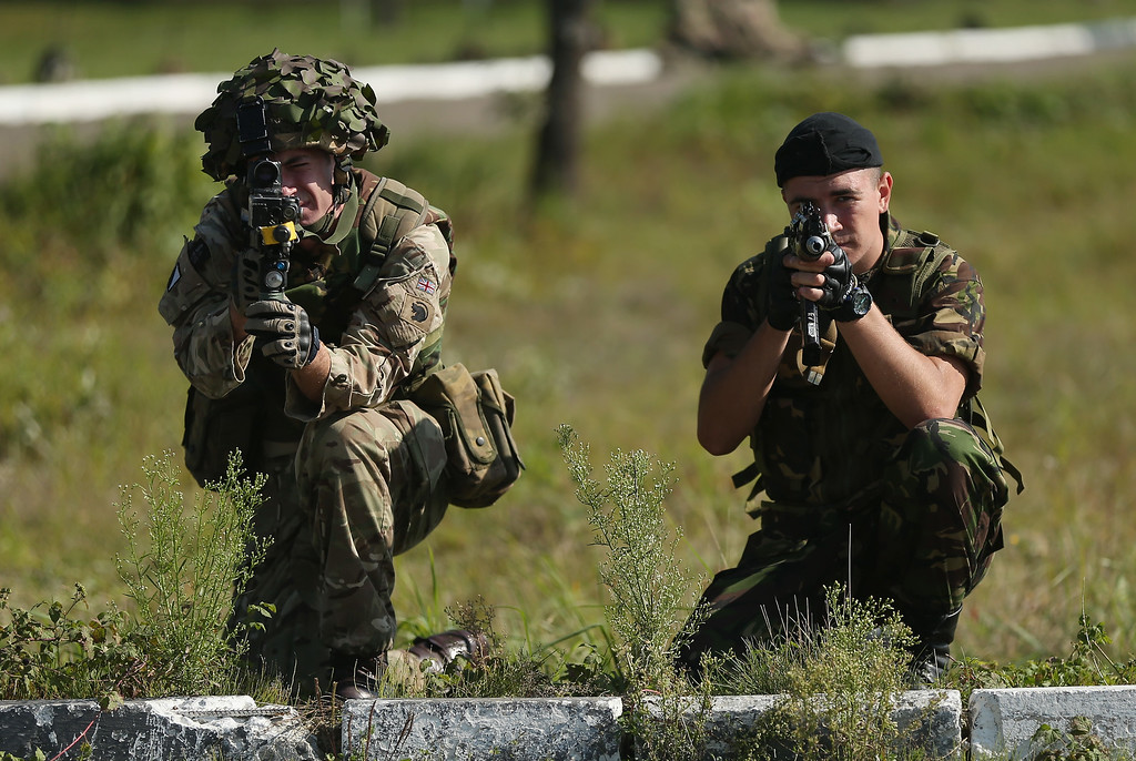 ". A Ukrainian soldier (R) and a member of the British Light Dragoons practice anti-IED (improvised explosive device) location and removal training on the second day of the ""Rapid Trident\"" NATO military exercises on September 16, 2014 near Yavorov, Ukraine.  (Photo by Sean Gallup/Getty Images)"