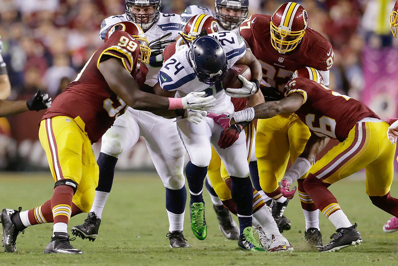 . Seattle Seahawks running back Marshawn Lynch (24) is stopped by Washington Redskins defensive end Jarvis Jenkins (99), nose tackle Chris Baker (92) and strong safety Bashaud Breeland (26) during the first half of an NFL football game in Landover, Md., Monday, Oct. 6, 2014. (AP Photo/Patrick Semansky)