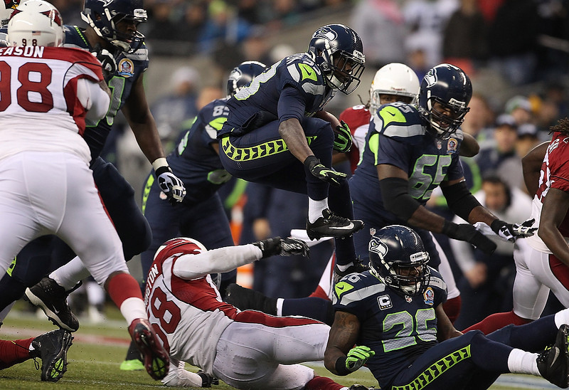 . Leon Washington #33 of the Seattle Seahawks hurdles Daryl Washington #58 of the Arizona Cardinals at CenturyLink Field on December 9, 2012 in Seattle, Washington.  (Photo by Kevin Casey/Getty Images)