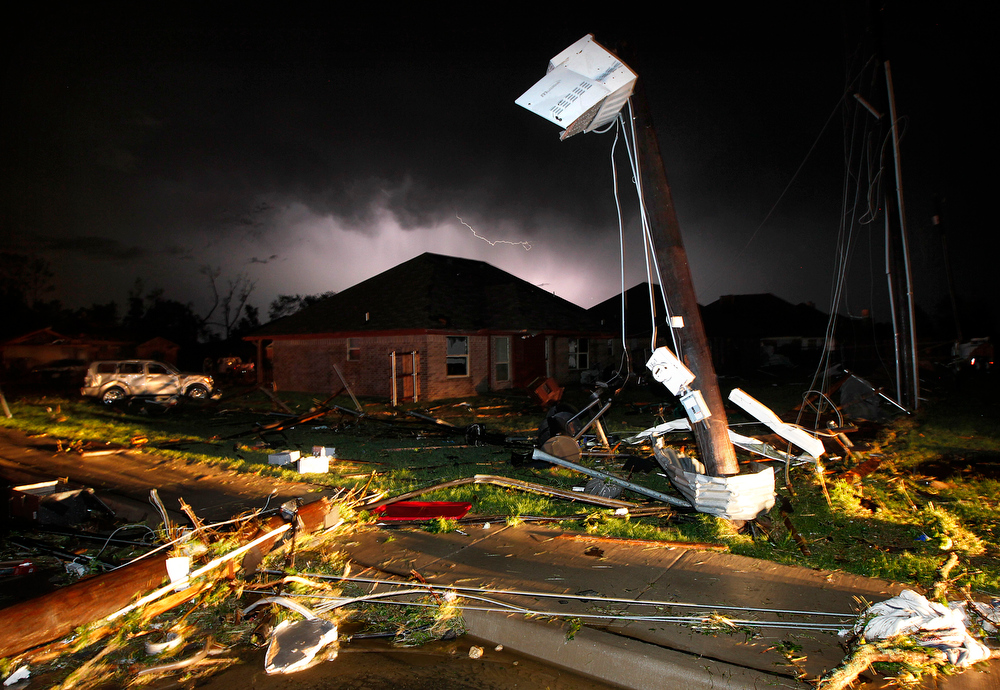 . Lightning strikes from a storm illuminates the sky where damage is strewn about the street and light pole near Hyde Park Lane at Country Club Rd. after a tornado in Cleburne, Texas, Wednesday night, May 15, 2013. Cleburne Mayor Scott Cain early Thursday declared a local disaster as schools canceled classes amid the destruction. (AP Photo/The Dallas Morning News, Tom Fox)