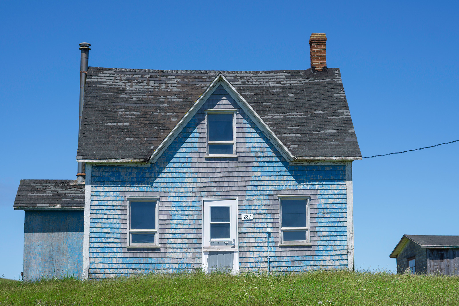 Even weather-worn, this blue house makes me anything but blue. One of many pretty wood slat houses in Havre-Aubert.