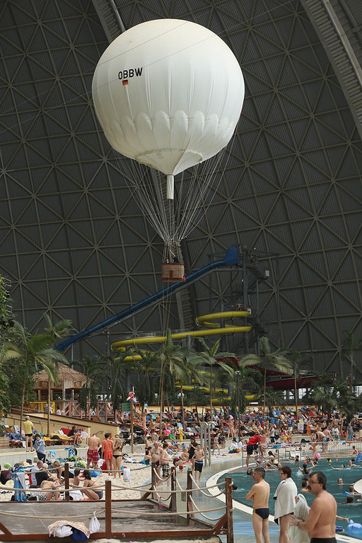 ". Visitors lounge at the ""South Sea\"" beach as a hot air balloon passes overhead at the Tropical Islands indoor resort on February 15, 2013 in Krausnick, Germany. Located on the site of a former Soviet military air base, the resort occupies a hangar built originally to house airships designed to haul long-distance cargo. Tropical Islands opened to the public in 2004 and offers visitors a tropical getaway complete with exotic flora and fauna, a beach, lagoon, restaurants, water slide, evening shows, sauna, adventure park and overnights stays ranging from rudimentary to luxury. The hangar, which is 360 metres long, 210 metres wide and 107 metres high, is tall enough to enclose the Statue of Liberty.  (Photo by Sean Gallup/Getty Images)"