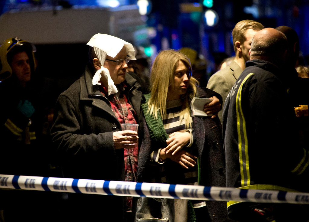 ". A  bandaged man comforts a woman  following an incident at the Apollo Theatre, in London\'s Shaftesbury Avenue, Thursday evening, Dec. 19, 2013, during a performance , with police saying there were ""a number\"" of casualties. (AP Photo by Joel Ryan, Invision)"