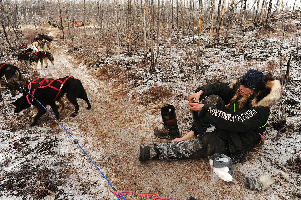 . Anna Berington changes her socks as she sits in the Iditarod trail in the middle of the Farewell Burn during the Iditarod Trail Sled Dog Race on Tuesday, March 4, 2014. (AP Photo/The Anchorage Daily News, Bob Hallinen)