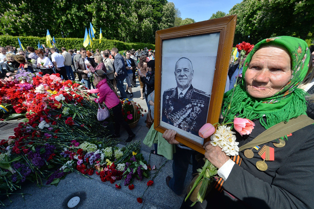 . An elderly veteran of WWII hold flowers and a portrait of the Soviet Army commander Marshal Georgiy Zhukov (Gueorgui Joukov) during a ceremony marking the Victory Day at the Unknown Soldier monument in the Ukrainian capital of Kiev on May 9, 2014. AFP PHOTO/ SERGEI SUPINSKY/AFP/Getty Images