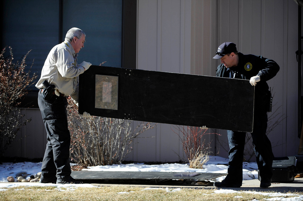 . Aurora Police investigators take a shield out of a town home next to 16005c  Ithaca Place in Aurora Saturday afternoon. The bodies of four people, including a gunman are dead at the scene following a standoff situation early Saturday morning. The Denver Post/ Andy Cross